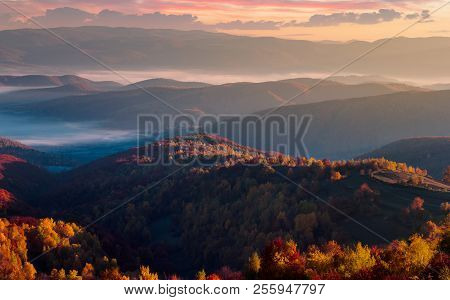 Gorgeous Red Sunrise In Mountains. Forested Hills In Colorful Fall Foliage. Fog In The Distant Valle