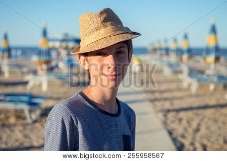 Young boy in hat posing at the summer beach. Cute smiling happy 12 years old boy at seaside, looking at camera. Kid's outdoor portrait over seaside.