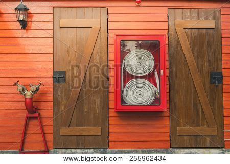 Fire Hose In Red Cabinet Hanging On Orange Wooden Wall. Fire Emergency Equipment Box For Safety And