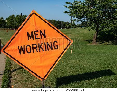 Men Working Constrction Sign Posted Up In A Park Area