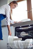 Dishwasher. Young woman in the Kitchen doing Housework. Wash-up poster