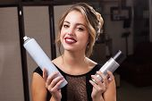 pretty smiling model with perfect makeup and coiffure holding two hair sprays and exploring them. concept of professional hairdresser products poster