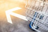 Shopping cart (trolley) over go forward arrowhead sign on the floor in supermarket or grocery store. Shopping lifestyle concept poster