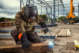 A Young  Man Welder In Brown Uniform, Welding Mask And Welders Leathers, Weld  Metal  With A Arc Wel