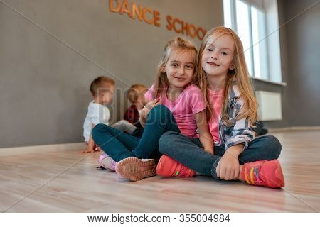 Portrait Of Two Happy And Cute Little Girls In Casual Clothes Hugging And Smiling At Camera While Si