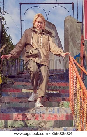 A Young Caucasian Woman In Warm Clothes Descends Down The Rainbow Stairs During A Winter Tourist Wal