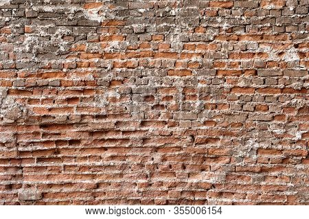 Surface Texture Of An Old Crumbling Red Brick Wall.