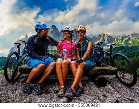 Cycling family outdoor adventure in Dolomites mountains landscape. Father, mother and daughter cycling MTB enduro trail. Outdoor sport activity.