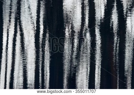 High Contrast Water Reflection Of Forest. Dark Trunks And Light Ripples. Abstract Blurred Shot.