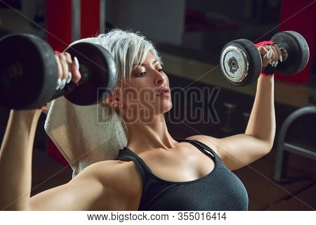 Athletic Woman Pumping Up Muscles With Dumbbells In The Fitness Room