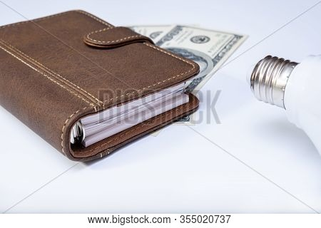 Energy Efficiency And Lowering, Reducing Concumption Of Electricity, Led Lamp, Notebook And Dollar B