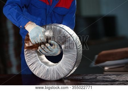 Worker In Overalls Prepares The Bearing For Transportation. Photo Without A Face. Bearing Production