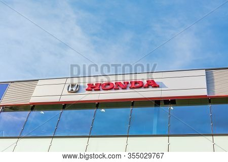 Honda Brand Logo On Bright Blue Sky Background Located On Its Dealer Office Building In Lyon, France