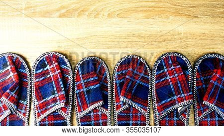 A Lot Of Colorful Comfortable, Cushioned, Checkered Disposable Slippers Are On The Wooden Floor. Top