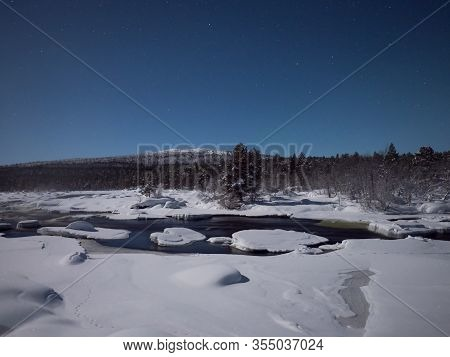 Moonlit Animal Footprints In Snow By Juutuanjoki River In Finland.