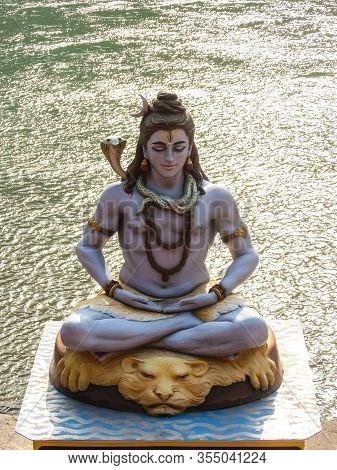 Rishikesh, India - Circa March 2018. Statue Of Shiva Sitting In Meditation On The Riverbank Of Ganga
