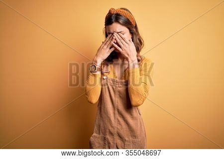 Young beautiful blonde girl wearing overall standing over yellow isolated background rubbing eyes for fatigue and headache, sleepy and tired expression. Vision problem