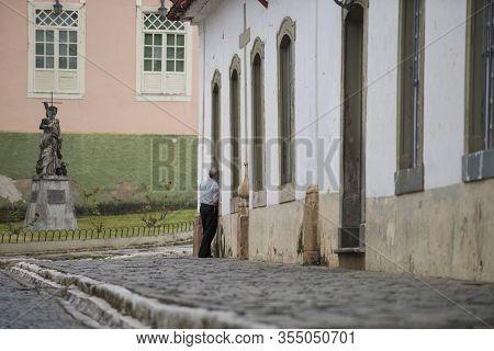 Sao Joao Del Rei, Minas Gerais, Brazil - March 05, 2016: Man Standing In A Cobblestone Street Of Sao