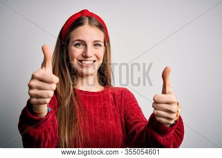 Young beautiful redhead woman wearing red casual sweater and diadem over yellow background approving doing positive gesture with hand, thumbs up smiling and happy for success. Winner gesture.