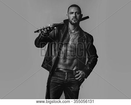 Brutal Attractive Bearded Biker Man With Tattooed Poses In Black Jacket. Copy Space. Handsome Bearde