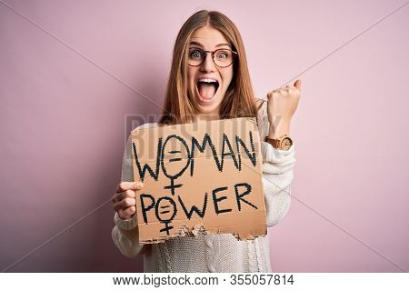 Young beautiful redhead woman asking for women rights holding banner over pink background screaming proud and celebrating victory and success very excited, cheering emotion