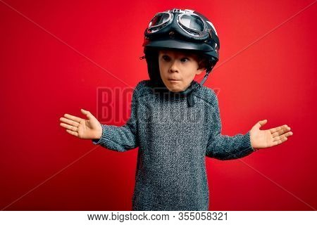 Young little caucasian kid wearing vintage biker motorcycle helmet and googles over red background clueless and confused expression with arms and hands raised. Doubt concept.