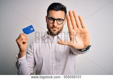 Young business man holding credit card over isolated background with open hand doing stop sign with serious and confident expression, defense gesture