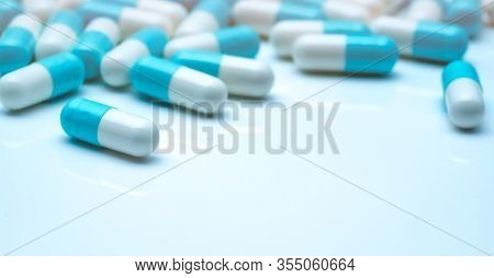 Selective Focus On Blue-white Capsule Pills. Capsule Pills Sperad On White Background. Pharmaceutica