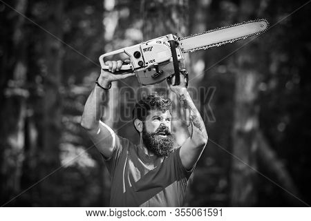 Lumberjack In The Woods With Chainsaw Axe. Handsome Young Man With Axe Near Forest. Chainsaw. Defore