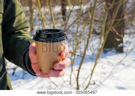 Man Holding A Coffee Paper Cup In Park With Snow Background . Coffee To Go In Winter Concept. Hot Dr