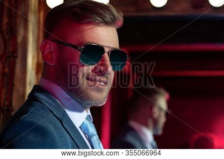 A portrait of a brutal handsome man in sunglasses. Men's beauty, fashion. Optics for men.