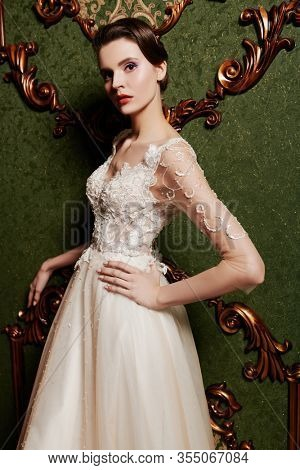 Portrait of a magnificent young woman in elegant white long dress. Luxurious dark apartments.  Wedding fashion.