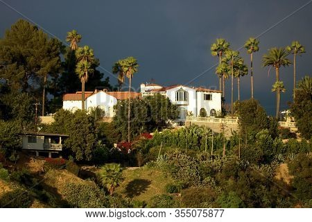 Spanish Colonial Style Hacienda Villa Surrounded By Palm Trees With Dark Storm Clouds Beyond Taken O