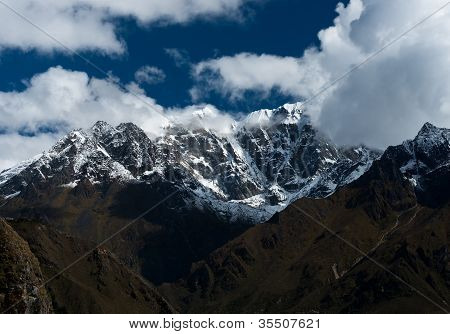 Snowbound mountain peaks and clouds in Himalayas. Pictured in Nepal poster