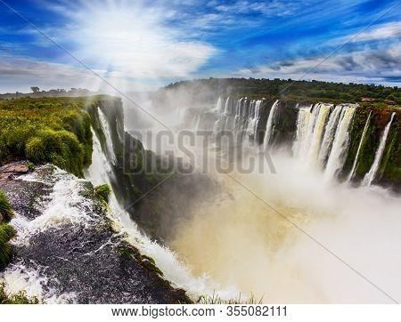 Parana River. The Garganta del Diablo/ Devil's Throat is the most grandiose part of the Iguazu Falls. The autumn sun shines through the clouds. Concept of active and extreme tourism