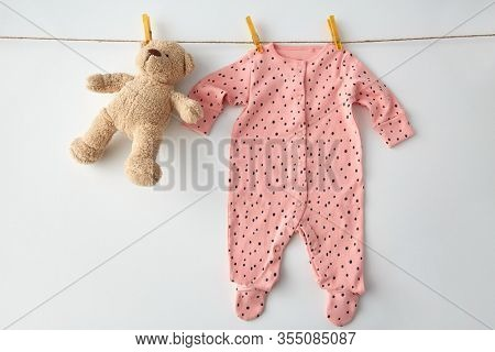 clothes, laundry, babyhood and clothing concept - pink long-sleeved bodysuit for baby girl with dot print hanging on clothesline with teddy bear and pins on white background