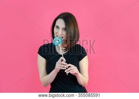 Portrait Of Atractive Happy Girl Biting Big Round Red Lollipop . Sweet Tooth. Teenager Girl Enjoying
