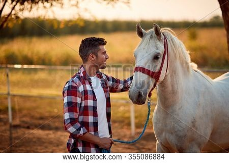 Loving tender moment between men and horse.Young smiling man and horse.