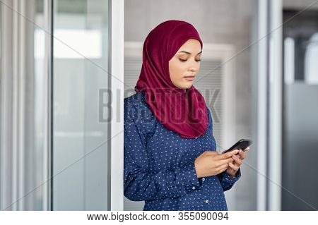 Young muslim businesswoman leaning against glass wall using smartphone. Islamic business woman in hijab using mobile phone in modern office. Arabic girl texting on cellphone to send email message.