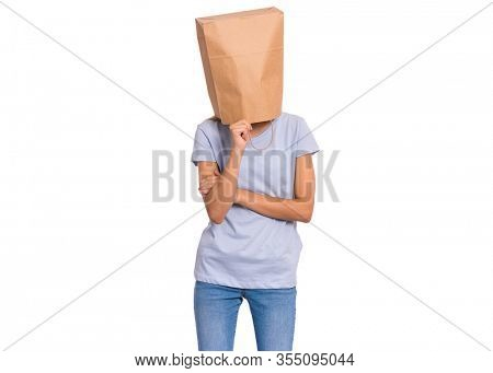 Pensive teen girl with paper bag over head. Thoughtful teenager cover head with bag holding hand near face isolated on white background. Child pulling paper bag over head.