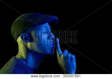 Black Man With Blue And Yellow Light, With Finger On Lips Making Silence Gesture, Closed Eyes, Weari