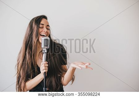 Young Beautiful Woman Sing In Vintage Microphone On White Background.