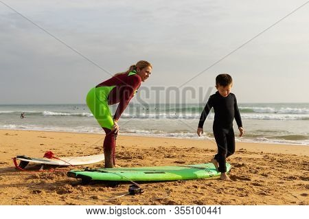 Mother And Son With Surfboards On Beach. Cheerful Middle Aged Woman Showing Little Son How Standing