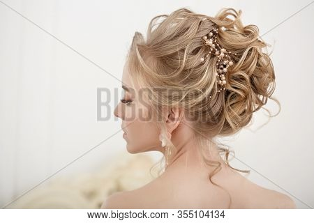 Bride with wedding flowers bouquet. Woman in wedding dress. Young fashion model with perfect skin, make up and Beautiful Hairstyle. Happy day. Marriage.