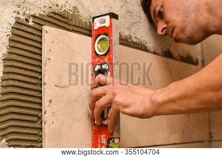 Tiler Checking Ceramic Tile With A Level Tool. Tiler Are Laying The Ceramic Tile On The Wall. Concep