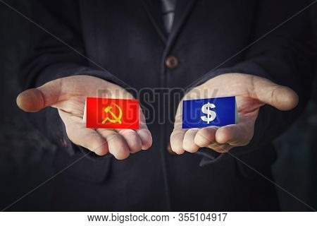 Choice Of Political System Is Communism Or Capitalism. Sign Hammer And Sickle Or A Dollar In The Han
