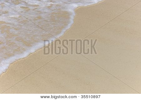 Soft wave of the sea on the sandy beach in the summer time