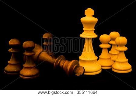 Black Team Surrender To White Team At The End Of The Game. Two Standard Chess Wooden Pieces On Black