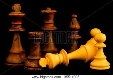 White Team Surrender To Black Team At The End Of The Game. Two Standard Chess Wooden Pieces On Black