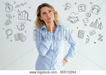 Office Girl Thinking Over Idea With Hand Drawn Business Sketches. Pensive Thoughtful Young Caucasian